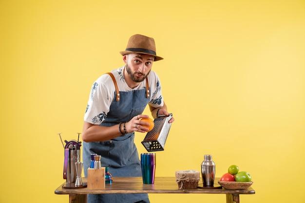 노란색 벽 클럽 나이트 바 알코올 음료 작업 색상에서 음료를 준비하는 전면 보기 남성 바텐더