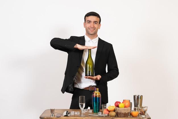 Barista maschio vista frontale in piedi davanti al tavolo con bevande in posa sul muro bianco notte bar maschio bevande alcoliche club