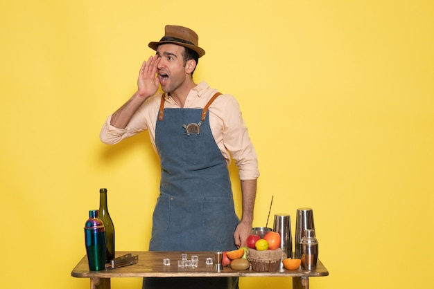 Вид спереди мужчина-бармен, стоящий перед столом с напитками и фруктами, зовет кого-то на желтой стене, ночной клуб, бар, мужской напиток
