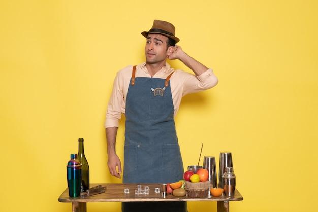 正面図男性バーテンダーが机の前に立って、黄色い壁に飲み物と果物のポーズをとる飲み物ナイトクラブジュースバー男性