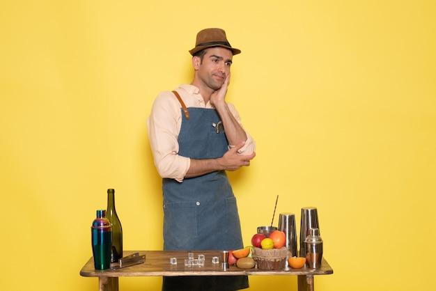 黄色い壁のドリンクバーナイトクラブジュースでポーズをとって飲み物や果物と机の前に立っている正面図男性バーテンダー