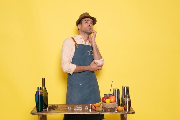 Вид спереди мужчина-бармен, стоящий перед столом с напитками и фруктами, позирует на желтой стене, пить ночной клуб, бар, мужчина