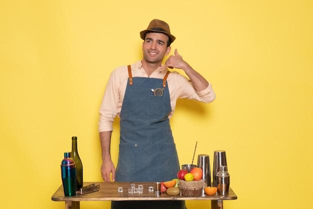 Вид спереди мужской бармен, стоящий перед столом с напитками и фруктами, улыбаясь на желтой стене, ночной клуб, бар, мужской напиток