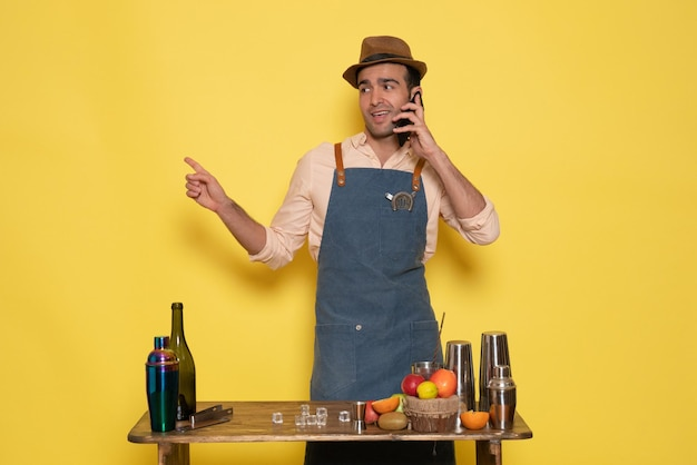 黄色い壁のドリンクバーナイトクラブジュースで電話で話している飲み物や果物と机の前に立っている正面図男性バーテンダー