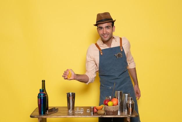 正面図男性バーテンダーが机の前に立って、黄色い壁のクラブバーに飲み物と氷を持って男性が夜のアルコールを飲む