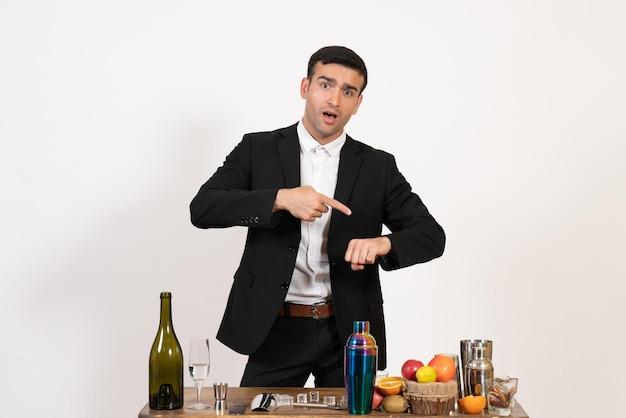 白い壁のバーの夜の飲み物クラブの男性のアルコールで彼の手首を見て飲み物とテーブルの前に立っている正面図男性バーテンダー
