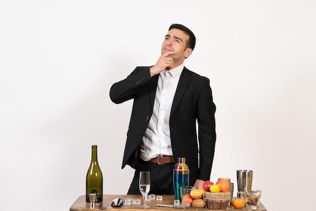 白い壁のバーの夜の男性のアルコールドリンククラブでポーズをとって考えている飲み物とテーブルの前に立っている正面図男性バーテンダー