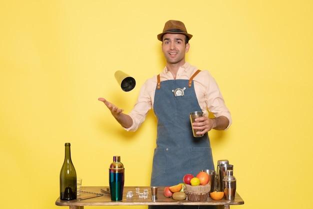 シェーカーで作業し、黄色い壁の夜のアルコールバークラブの男性の飲み物で飲み物を作る正面図の男性バーテンダー