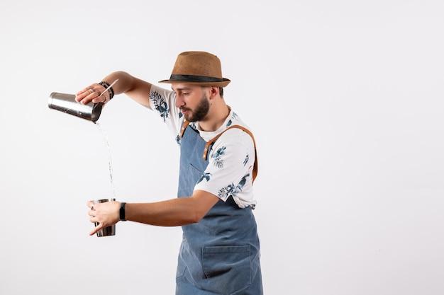 Barista maschio di vista frontale che lavora con l'agitatore che fa bevanda sulla barra di colore di lavoro delle bevande alcoliche del night club della parete bianca