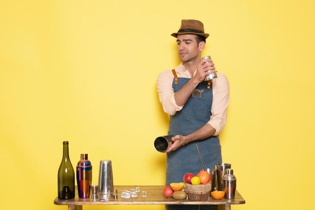 전면 뷰 남성 바텐더는 셰이커로 작업하고 노란색 벽 밤에 음료를 만드는 남성은 알코올 바 클럽을 마신다