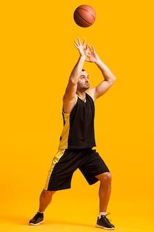 Vista frontale del dunking maschio del giocatore di pallacanestro