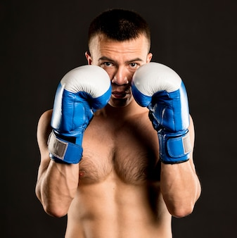 Front view of male boxer posing with protective gloves