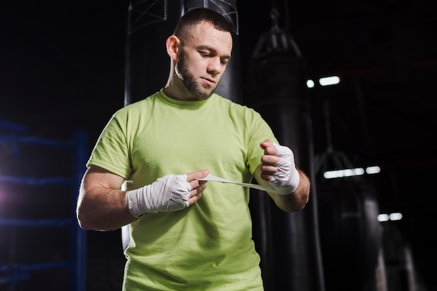 Front view of male boxer in t-shirt putting on protection for hands