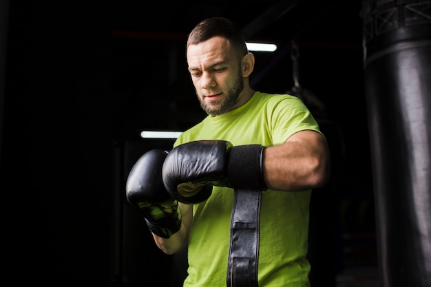 Front view of male boxer in t-shirt with protective gloves