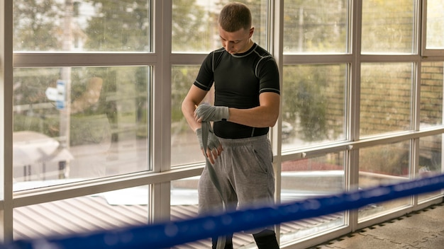 Front view of male boxer wrapping his hands before training in the ring