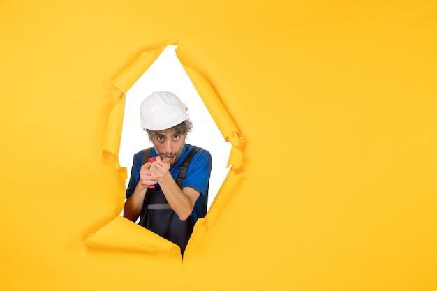 黄色の背景にドリルを保持している正面図男性ビルダー
