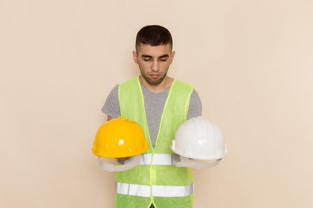Front view male builder holding pair of helmets on light background