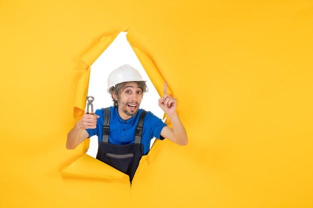 黄色の背景にペンチを保持している正面図男性ビルダー
