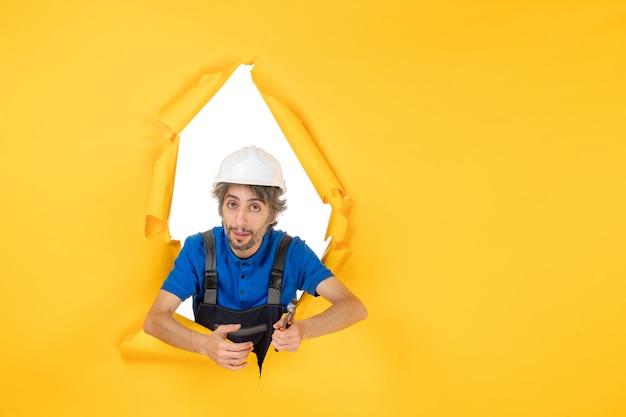 Costruttore maschio di vista frontale che tiene le pinze su sfondo giallo