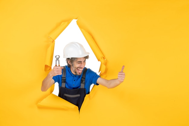 Front view male builder holding pliers on yellow background