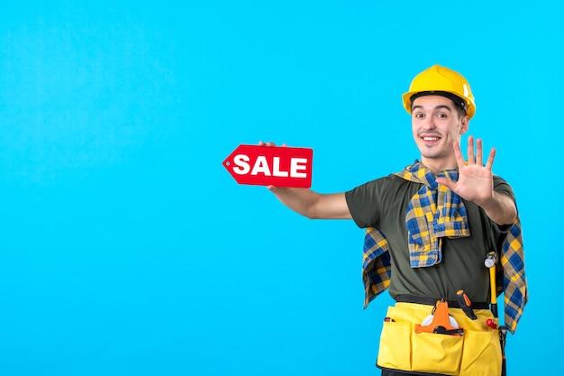 파란색 배경 평면 건축 생성자 색상 작업자 건물 돈 속성에 판매 쓰기를 들고 전면보기 남성 빌더