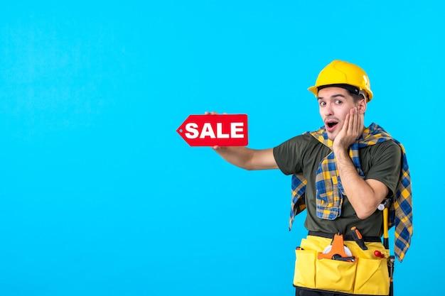 파란색 배경 평면 건축 생성자 작업자 건물 색상에 판매 쓰기를 들고 전면보기 남성 작성기