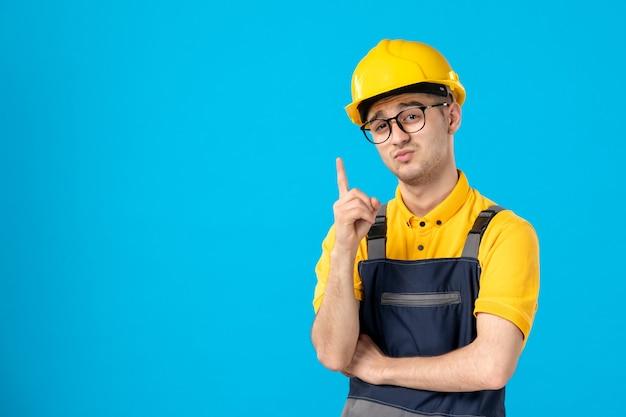 Строитель-мужчина в униформе и шлеме, вид спереди, имеет идею на синем