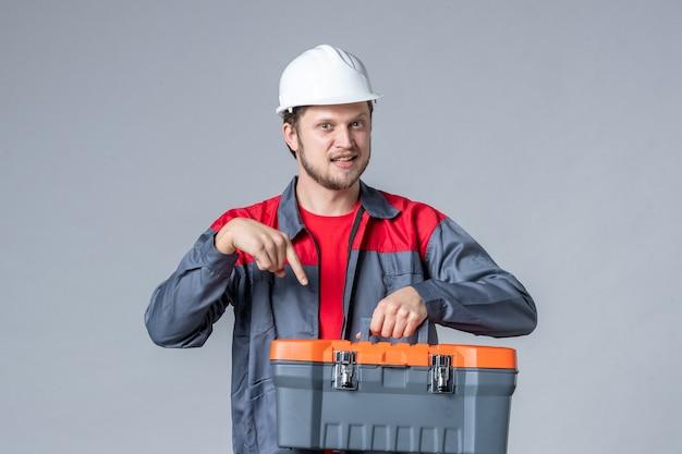 灰色の背景に制服とヘルメット保持ツールケースの正面図男性ビルダー