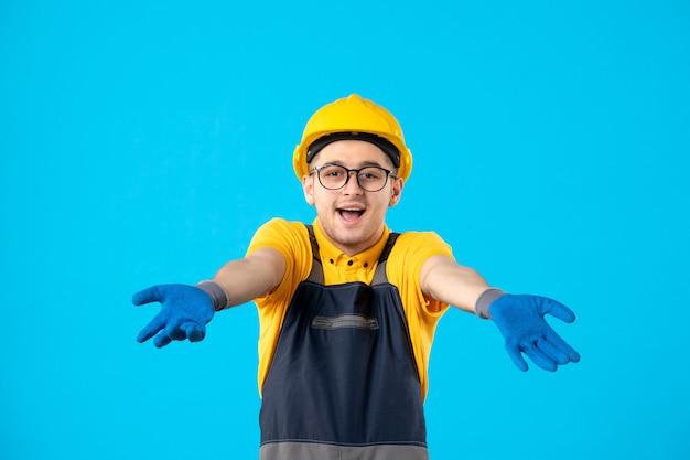 Вид спереди мужчина-строитель в форме и шлеме на синем