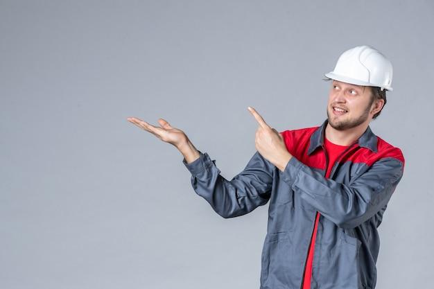 灰色の背景に制服とヘルメットの正面図男性ビルダー