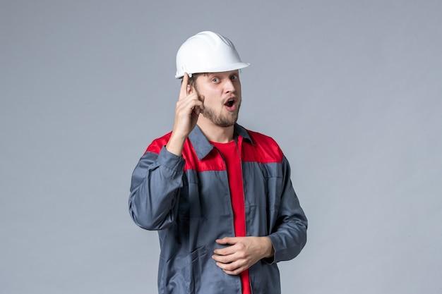 Вид спереди мужчина-строитель в форме и шлеме на сером фоне