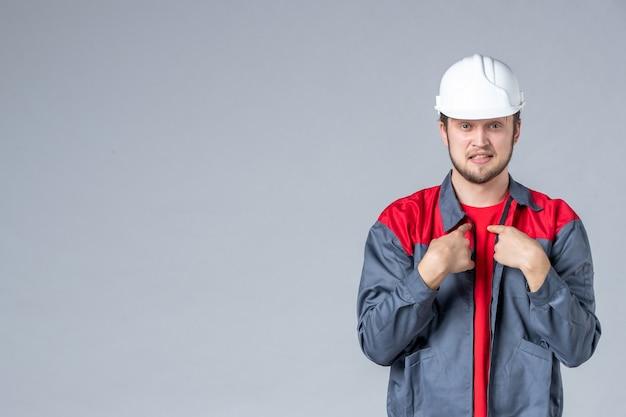 制服を着た正面図の男性ビルダーと明るい背景のヘルメット