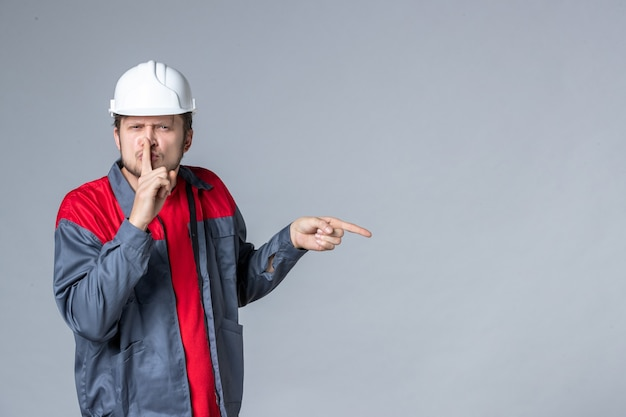Вид спереди мужчина-строитель в форме и шлеме на светлом фоне