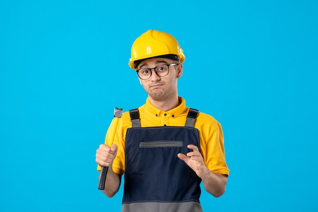 Строитель-мужчина в униформе и шлеме с молотком на синем, вид спереди