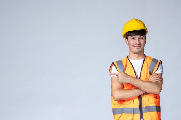 Вид спереди мужчина-строитель в форме и желтом шлеме на серой стене