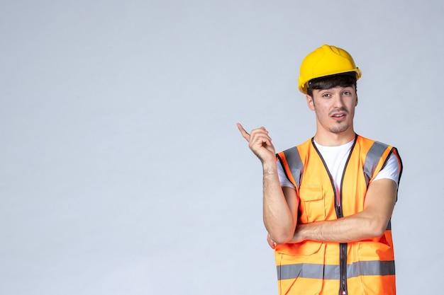 白い壁に制服と黄色のヘルメットの男性ビルダーの正面図
