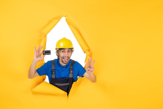 黄色の背景に黒い銀行カードを保持している制服を着た男性ビルダーの正面図