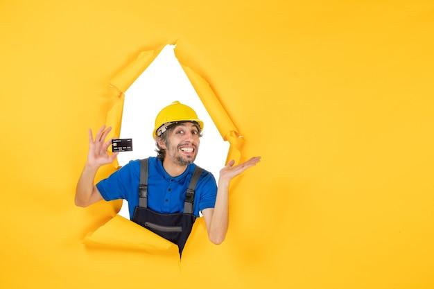 노란색 배경에 검은색 은행 카드를 들고 제복을 입은 전면 보기 남성 빌더