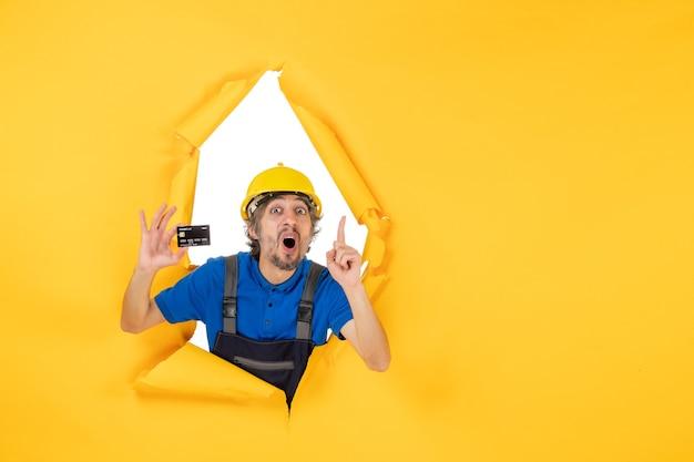 Вид спереди мужчина-строитель в униформе с черной банковской картой на желтом фоне