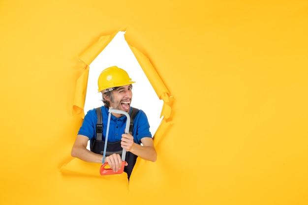 黄色の背景に弓鋸を保持している制服を着た男性ビルダーの正面図
