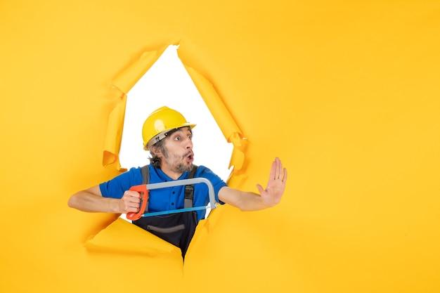 Строитель-мужчина в униформе, держащий луковую пилу на желтом фоне, вид спереди