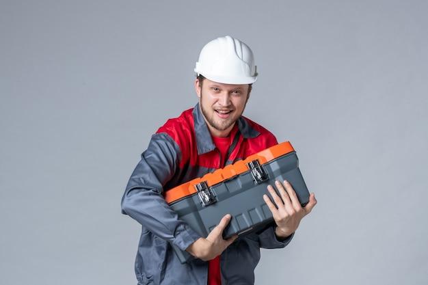 회색 배경에 무거운 도구 케이스를 들고 제복을 입은 전면 보기 남성 빌더