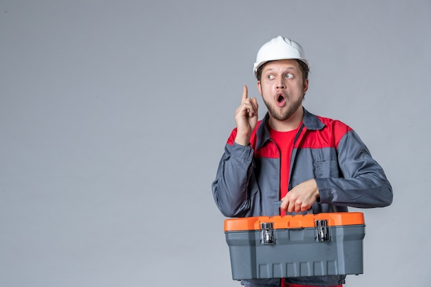 均一な保持ツールケースの正面図男性ビルダーは灰色の背景にアイデアを持っています