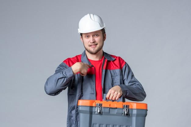 灰色の背景に均一な保持ツールケースの正面図男性ビルダー