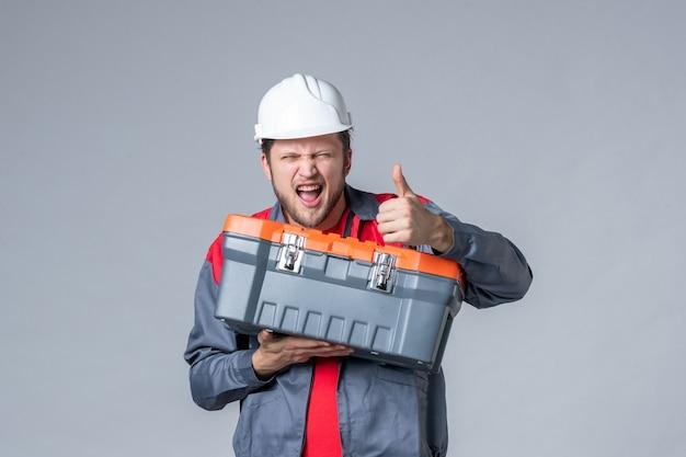Мужчина-строитель в униформе, держащий чемодан с инструментами на сером фоне, вид спереди