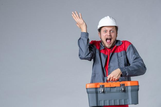 회색 배경에 흥분된 얼굴로 도구 케이스를 들고 있는 유니폼을 입은 남성 빌더