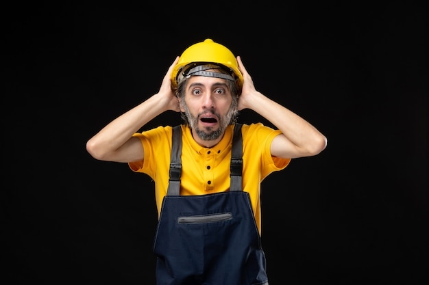 Мужчина-строитель в униформе на черной стене вид спереди