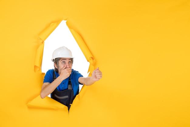 Мужчина-строитель в униформе на желтом фоне, вид спереди