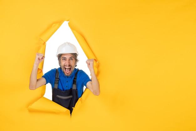 黄色の背景に制服を着た正面図男性ビルダー