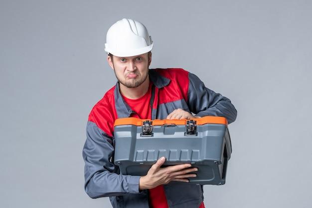 Мужчина-строитель в униформе, вид спереди, пытается открыть чемодан с инструментами на сером фоне